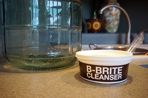 b-brite cleaner for cider making in front of a glass carboy