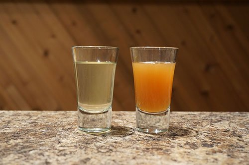 two glasses filled with cider, one is cloudy and one is clear