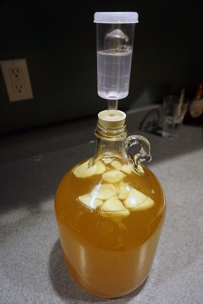 a carboy and airlock with fermenting hard cider