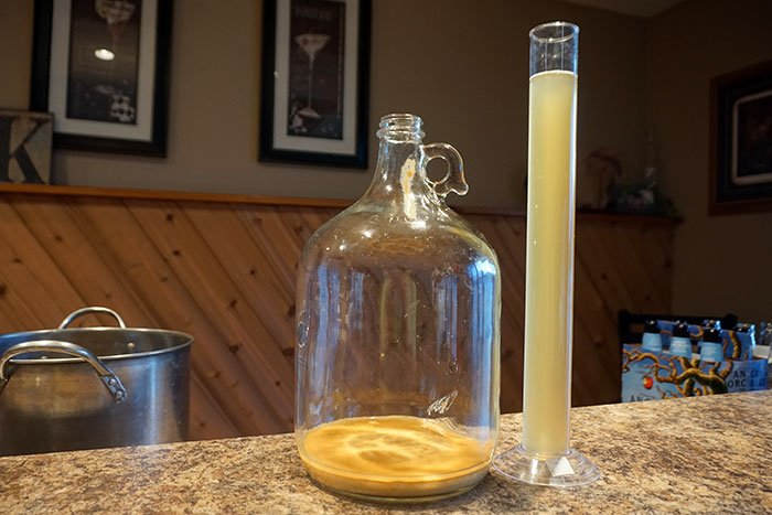 a clear glass carboy with used yeast in the bottom