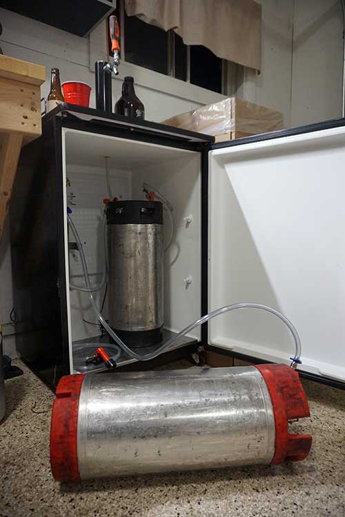 a corney keg on its side being rolled to force carbonate cider