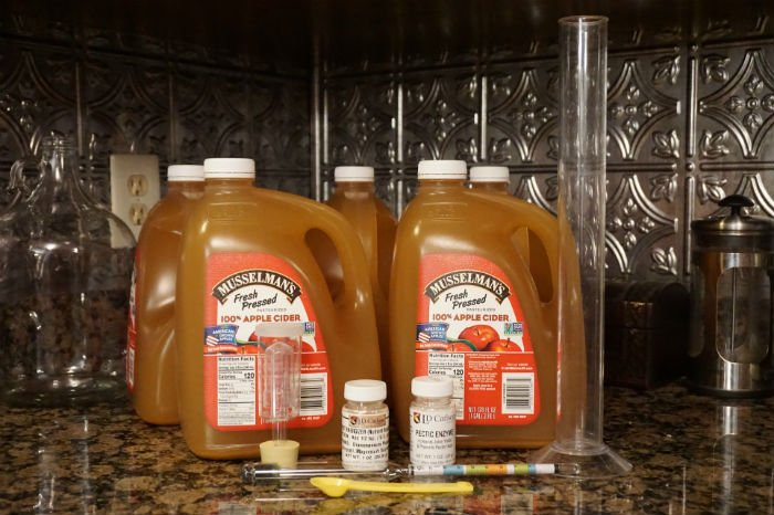 jugs of apple cider and equipment for making hard cider